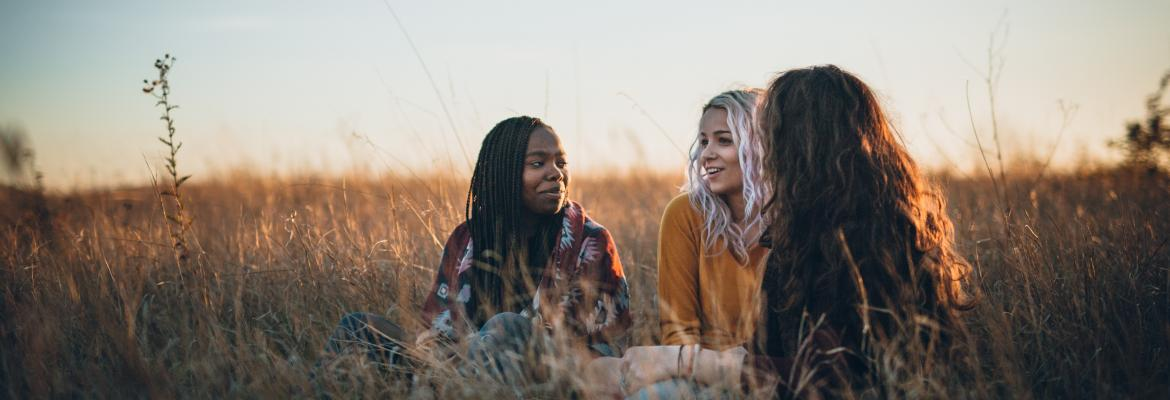 Three women sitting in a field chatting at sunset
